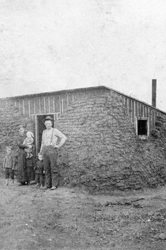 A pioneer family posing outside their sod and mud home in the late 19th century.