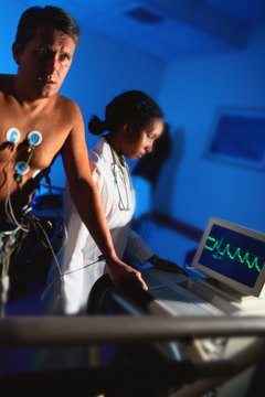 During a stress test, a patient walks on a treadmill while a technician monitors changes in his heart.