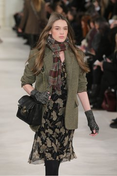 A model expertly balances frilly and funky with a floral dress and ladylike purse paired with a utilitarian jacket and a boldly clashing scarf.