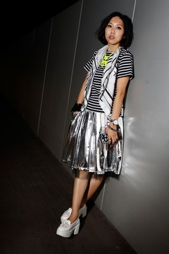Fashion blogger Faye Tsui rocks a pair of white platform loafers with a metallic skirt and striped tee for a funky look.