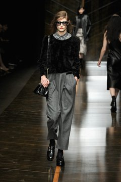 A model wears dark gray pants with a black sweater during Milan Fashion Week in 2014.
