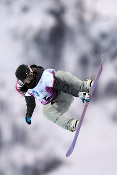 A competitor at the 2013 women's World Cup snowboard competition bends into the jump.