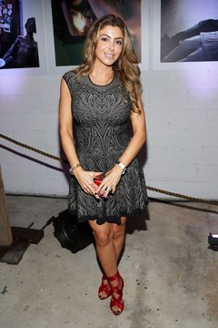 """Real Housewife"" Larsa Pippen accents an LBD with bright red at an event for Art Basel in Miami in December 2013."