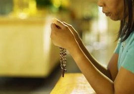 Praying the rosary, done here with a set of beads, is not mandatory at funerals.