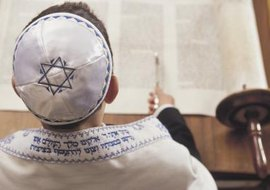A Jewish boy celebrates his bar mitzvah by reading from the torah.