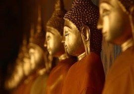 A row of Buddha statues adorn the exterior of a temple.