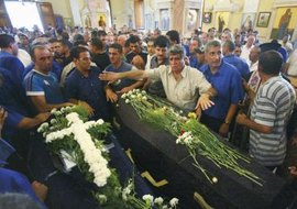 Mourners place flowers on top of the casket in Greek Orthodox tradition.