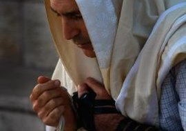 A religious Jew wearing both a tefillin and a tallit.