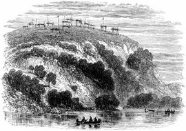 Native Americans rowing canoes below cemetery grounds.