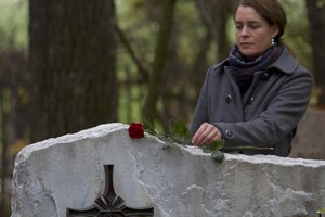 Woman holding rose at gravesite.