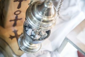Incense smoke cascades from a thurible.