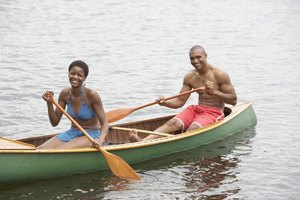 Couple canoeing with two wooden boat oars.