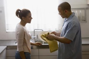 Young man and woman talking to each other while doing the dishes.