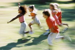 A group of kids running on the lawn.