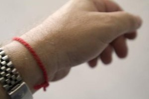 A close-up of a kabbalah red string tied around a person's wrist.