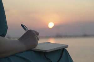 A woman sitting by the lake while writing a letter at sunset.