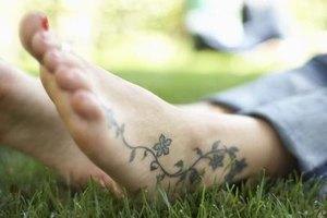 Tattooed barefoot in grass.