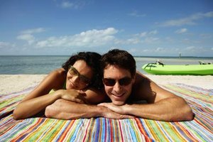 Couple smiling while lying on beach.