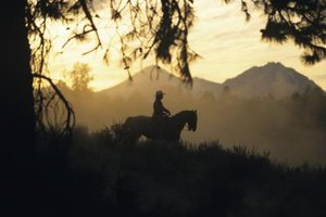 Silhouette of man riding horse in the distance.