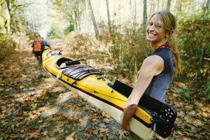 A happy couple carrying a kayak together on a trail.