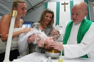 Priest baptise baby as mother and godmother assist in Mississippi.