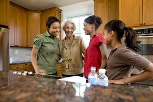 A family is talking to one another at the kitchen island.
