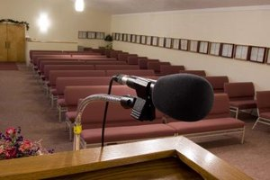 A close-up of a microphone on the podium in front of church pews.