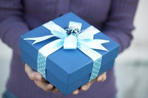 Anonymous person holding a blue box with a ribbon.