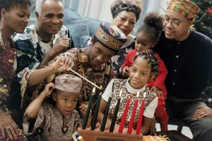 Family celebrating Kwanzaa while lighting the seven Kwanzaa candles