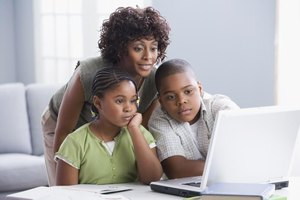 Mother looking over children's shoulders at laptop.