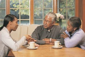 Family members having a discussion around the kitchen table.