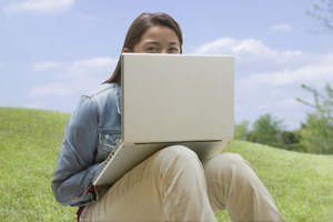 A woman is sitting outside using her computer.