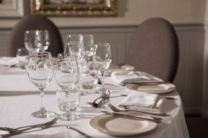 Fancy table set up with glasses, plates and silverware