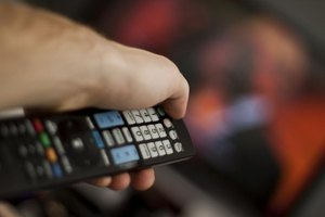 Close-up of a hand holding a remote control in front of a television