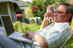 A man using his laptop in a lawnchair in the backyard.