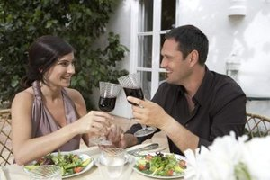 Couple toasting glasses at dinner table.
