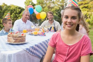 Girl having birthday cake with her family outside