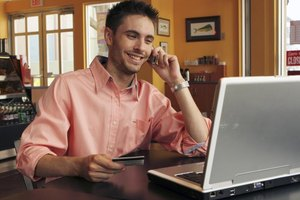 Man making phone call while holding credit card and looking at laptop screen.