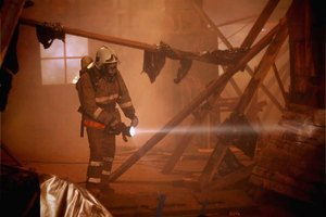 A firefighter searches a burned home.