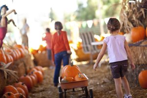 Young girls are pulling around pumpkins at a fall festival.