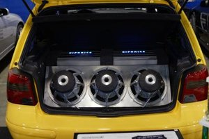 Three subwoofers in a car trunk.