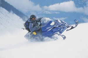 Man turning a fast moving snowmobile.