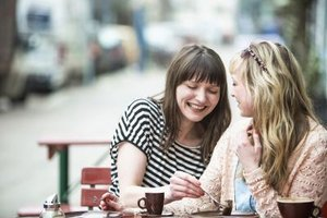 Two friends laughing together at an outdoor cafe.