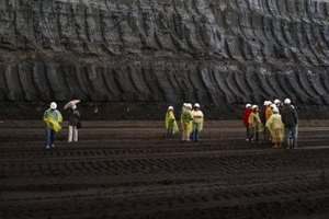 Workers stand in an open pit coal mine.