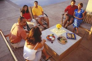 Couples enjoying appetizers on a poolside patio.