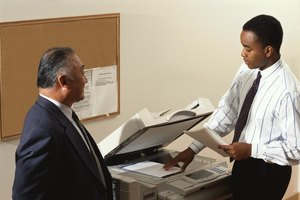 A man is putting a paper in the copier.