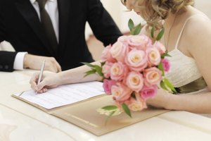 A bride and groom signing a marriage affidavit.