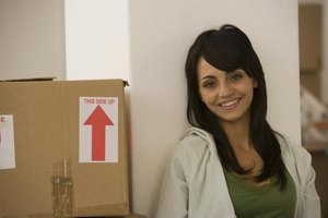 A smiling woman leaning against a wall next to a stack of moving boxes.