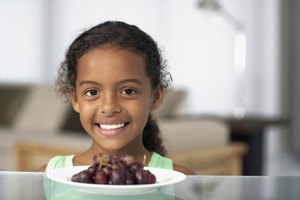 Smiling child behind small plate of grapes.