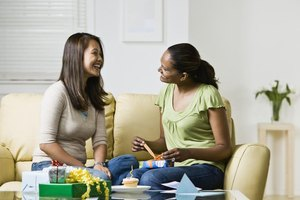 A woman opening a gift on the sofa with her friend.